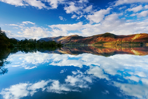 View across the lake of a white house in the Lake District. Credit: VisitEngland/AlexHare